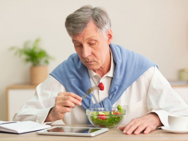 Senior Gentleman Eating Vegetable Salad Reading News On Tablet Computer Sitting At Workplace Indoor. Selective Focus